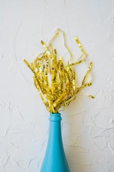 Ouropel espalhadas de garrafa azul
