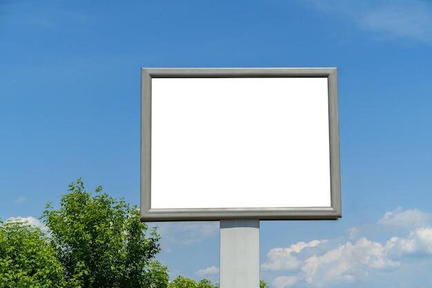 Outdoor com espaço em branco para layouts e cartazes na rua entre as árvores contra o céu azul e as árvores.