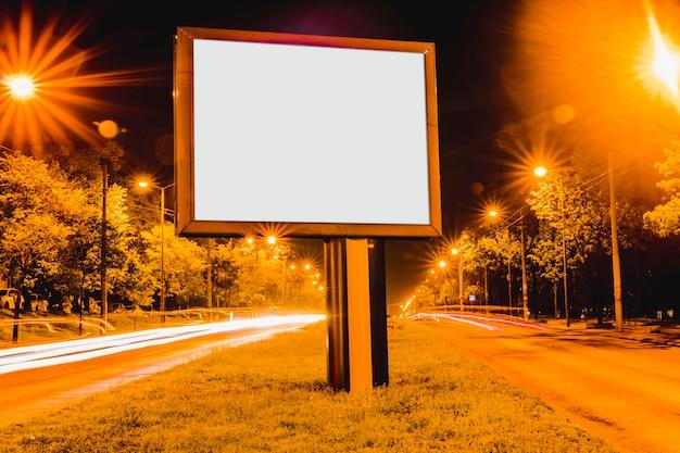 Outdoor de propaganda em branco com trilhas leves no centro da cidade à noite