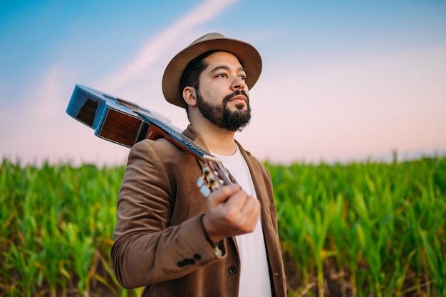 Outdoor de um jovem latino-americano e violão. músico brasileiro.