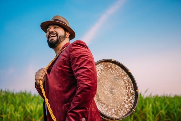Outdoor de um jovem latino-americano e zabumba. músico brasileiro.