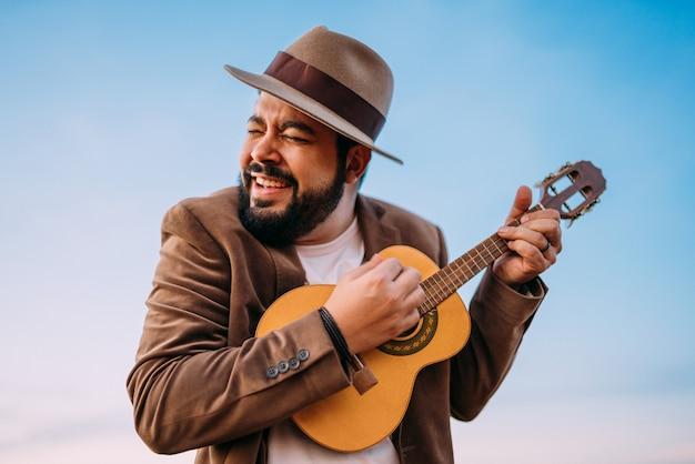 Outdoor de um jovem latino-americano tocando cavaquinho ou cavaquinho. músico brasileiro.