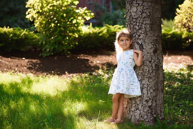 Outdoorin pequeno bonito da moça um parque.