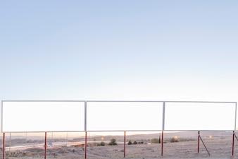 Outdoors de publicidade em branco perto da estrada contra o céu azul