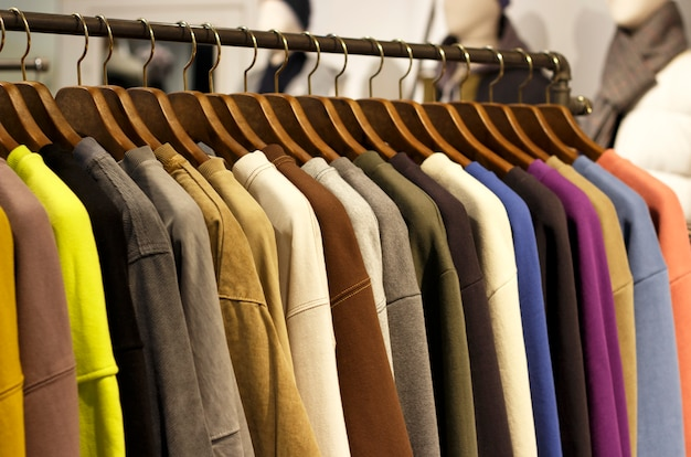 Outerwear multicolorido pendurado em cabides na loja close-up, vista lateral