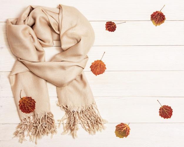Outono aconchegante composição com folhas secas de álamo tremedor e cachecol bege pastel