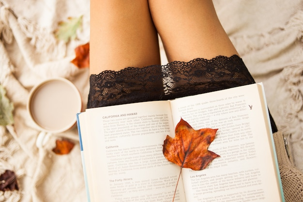 Outono ainda a vida. vista de cima. a menina lê um livro aberto enquanto está sentado em uma manta