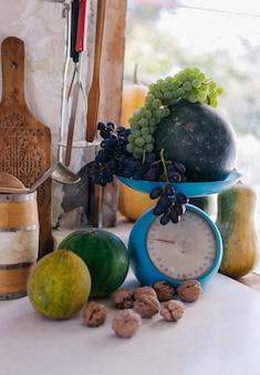 Outono ainda vida com abóboras, nozes, melões, melancia e uvas em uma escala para escalar e sobre uma mesa de madeira branca.