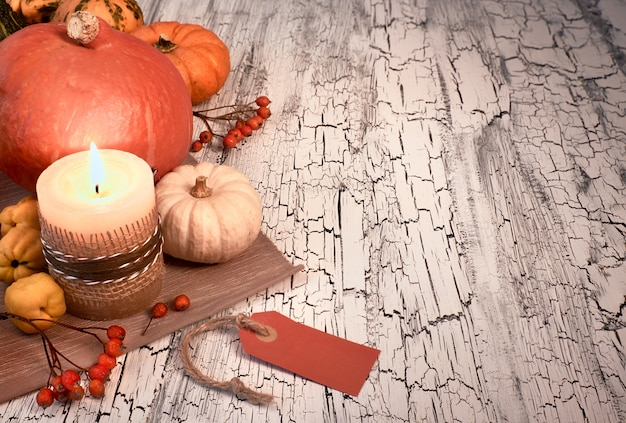 Outono ainda vida com abóboras, vela acesa e etiqueta de papel