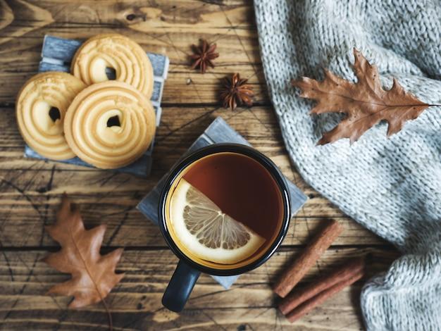 Outono ainda vida com uma xícara de chá, biscoitos, blusa e folhas na mesa de madeira.