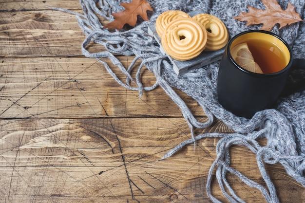 Outono ainda vida com xícara de chá, biscoitos, camisola e folhas na superfície de madeira.