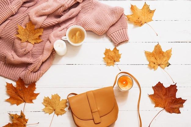 Outono ainda vida, folhas amarelas, abóbora, velas, suéter tricotado em uma vista superior branca.