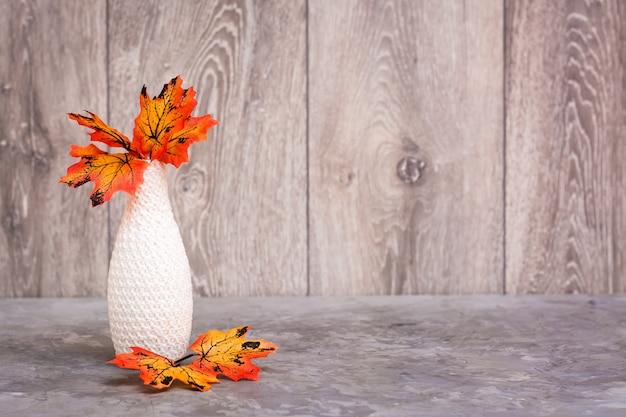 Outono ainda vida. um vaso com folhas de bordo laranja em cima da mesa. esquema de cores branco-laranja-bege. copie o espaço
