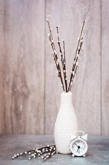 Outono ainda vida. um vaso com galhos de salgueiro e um despertador branco estão sobre a mesa. esquema de cores branco-cinza-bege. copie o espaço