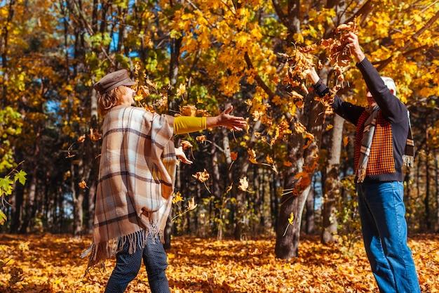 Outono. casal jogando folhas na floresta de outono
