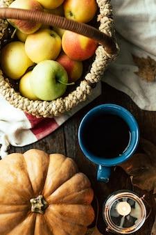 Outono, chá, abóboras e maçãs em uma mesa de madeira