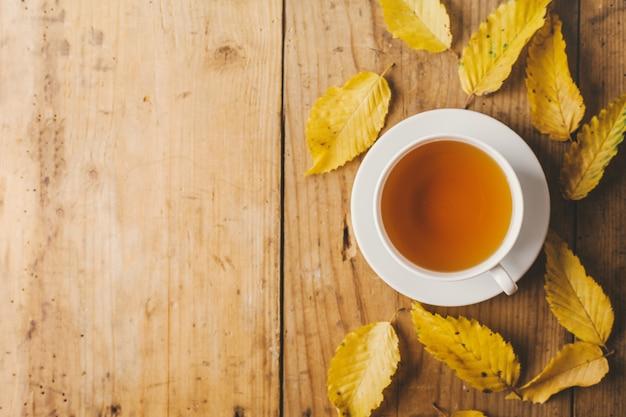 Outono chá na mesa de madeira com folhas