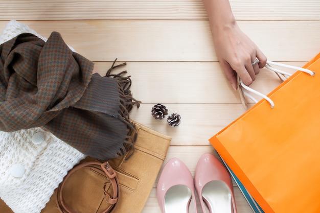 Outono chega, a mão de uma mulher segurando sacolas com roupas da moda em fundo de madeira