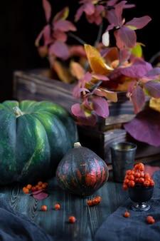 Outono colheita de abóboras em uma mesa de madeira escura com folhas de outono