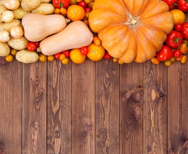 Outono colheita de legumes na superfície de madeira