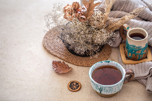 Outono composição em casa com uma bela xícara de chá de cerâmica na mesa. artigos decorativos no interior.