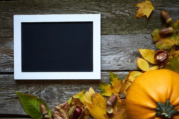 Outono de ação de graças, superfície de madeira com abóboras, folhas murchas, bolotas, castanhas e uma moldura para inscrições