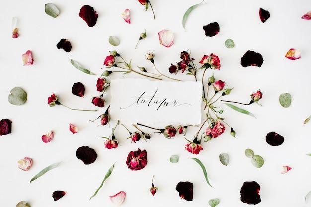 Outono de palavras escritas em estilo de caligrafia em papel com rosas cor de rosa, vermelhas, eucalipto e folhas em branco