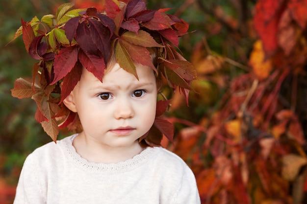 Outono fechar o retrato da menina. menina bonita com folhas de uva vermelhas no outono park. atividades de outono para crianças. dia das bruxas e diversão de tempo de ação de graças para a família.