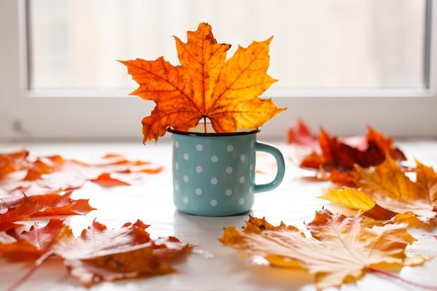 Outono. folhas caídas e uma caneca rústica de chá quente