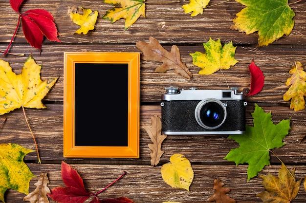Outono folhas, câmera e moldura na mesa de madeira.