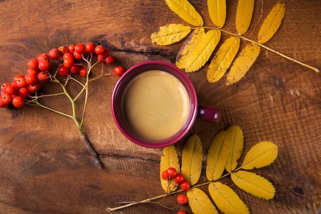 Outono, folhas e bagas de rowan, uma xícara de café fumegante quente sobre uma mesa de madeira vista superior.