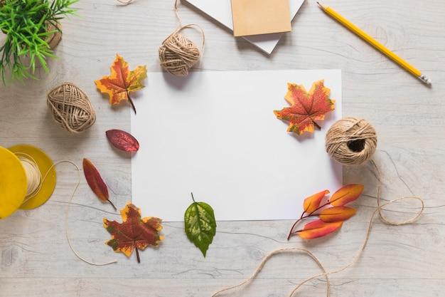 Outono folhas falsas em papel branco e carretel de corda sobre a mesa de madeira