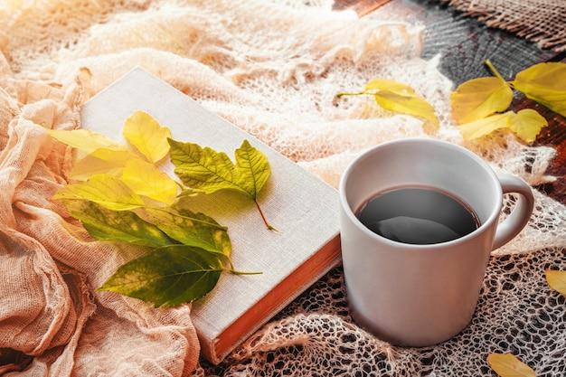 Outono folhas folhas de café quente fumegante e um lenço quente no fundo da mesa de madeira sazonal m.