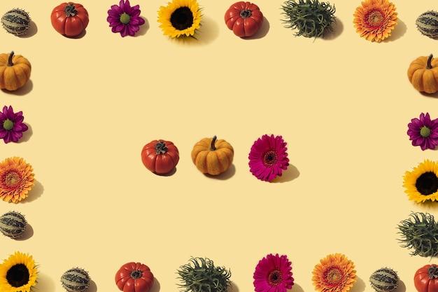 Outono fundo amarelo iluminado pelo sol com abóboras laranja, girassol e brilhantes flores sazonais. colheita plana leiga ou conceito de halloween. layout criativo de vegetais coloridos. copie o espaço.