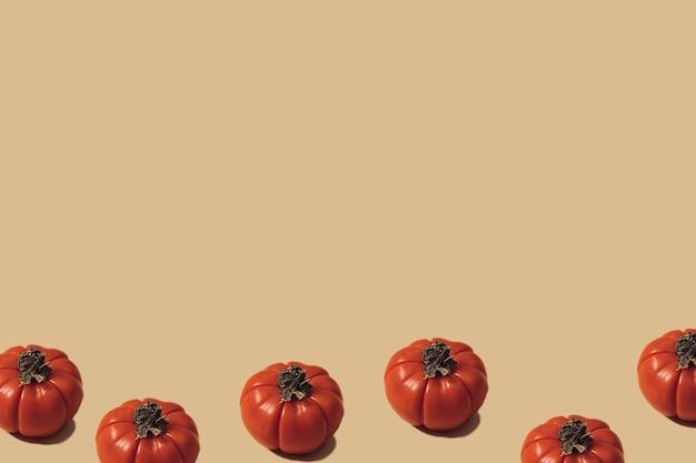 Outono fundo amarelo iluminado pelo sol com abóboras ou tomates. colheita plana leiga ou conceito de halloween. layout criativo de vegetais coloridos. copie o espaço.