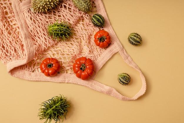 Outono fundo amarelo iluminado pelo sol com abóboras, physalis, tomates e frutas verdes da estação em uma bolsa de malha eco rosa. colheita plana leiga ou conceito de halloween. layout criativo de vegetais coloridos.