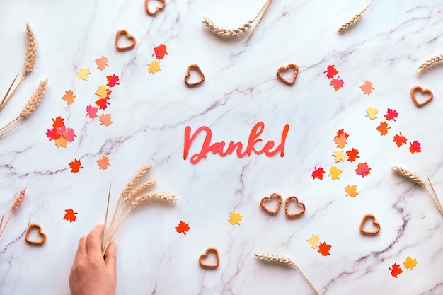 Outono fundo sazonal com espigas de trigo e confetes de papel. o texto em papel danke significa obrigado em alemão. plano deitado na mesa de mármore branco.