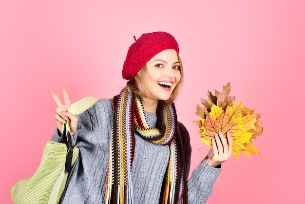 Outono. humor de outono. folhas de outono. mulher sorridente com folha de plátano. mulher com folhas de outono mostra sinal de paz. folha de bordo amarela. mulher mostra sinal de paz. isolado. assinar v.