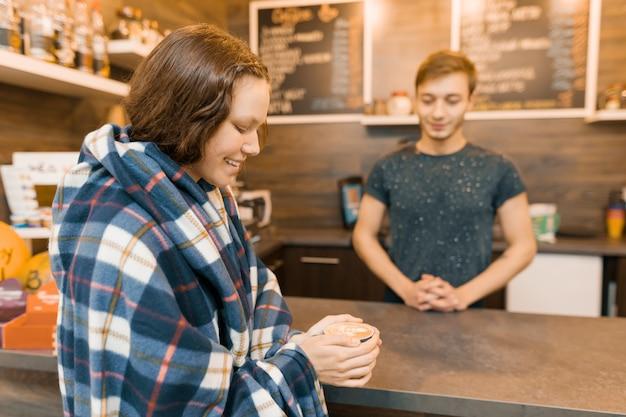 Outono inverno retrato de jovem adolescente coberto com manta de lã xadrez na cafeteria