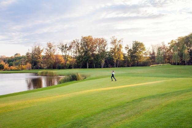Outono, lago, campo de golfe. jovem adulta correndo na grama verde do campo de golfe. a liberdade da garota. exterior