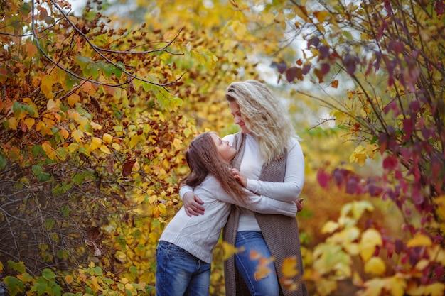 Outono, mãe e filha no parque de outono