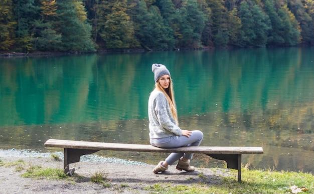 Outono menina bonita posando perto do lago de montanha. paisagem de outono na floresta.