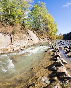 Outono montanha pedregosa vista para o rio com árvores multicoloridas à beira-rio. dois tiros costuram a imagem.