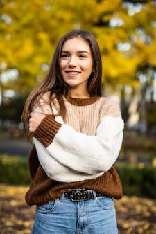 Outono mulher de suéter no parque outono. clima quente e ensolarado. conceito de outono