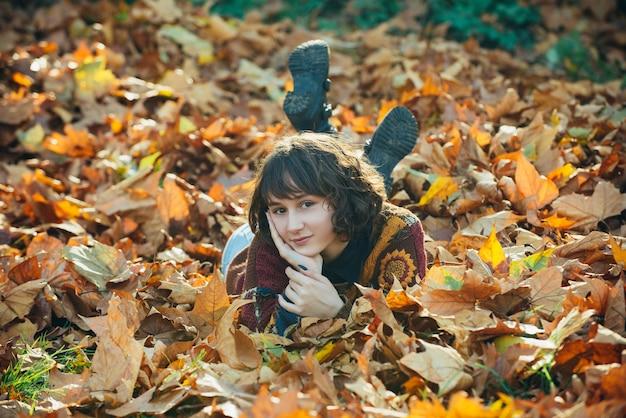 Outono mulher deitada sobre as folhas e sorrindo o retrato de uma menina no outono laranja deixa quente sunn.