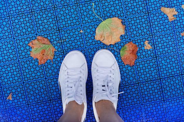 Outono na cidade, close-up das pernas de tênis e primeiras folhas amarelas caídas, superfície azul do fundo do playground