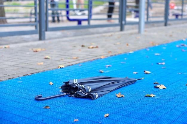Outono na cidade, close-up de um guarda-chuva e primeiras folhas amarelas caídas, superfície azul do fundo do playground