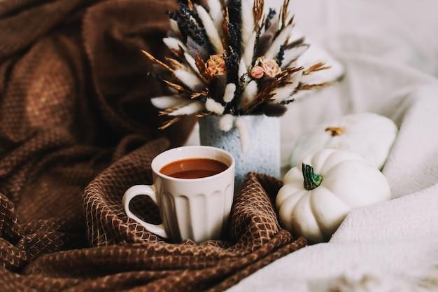 Outono natureza morta com uma xícara de café com flores e abóboras em uma manta aconchegante na cama elegante de outono ...