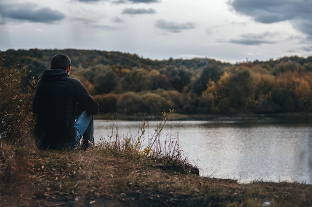 Outono nublado escuro. o cara sentado na margem do rio por trás. solidão