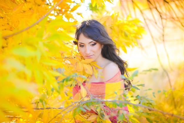 Outono, outubro, uma linda garota de pé em folhas amarelas em um parque close-up